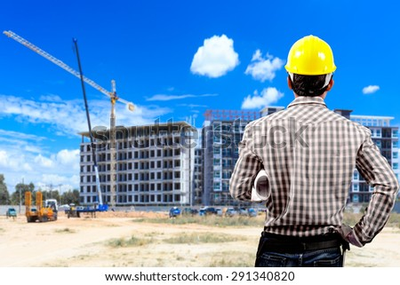 Foreman holding blueprint and the blurred construction site  - stock photo