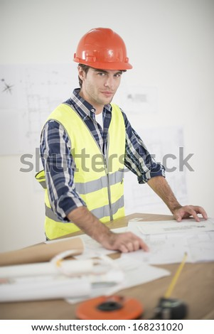 foreman in his office reviewing building plans - stock photo