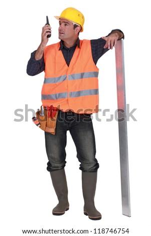 foreman standing in studio using talkie walkie - stock photo