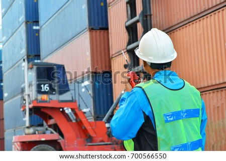 foreman supervisor working in yard of container takes control,command by radio walkie talkie for the lifting of containers unit by forklift in background