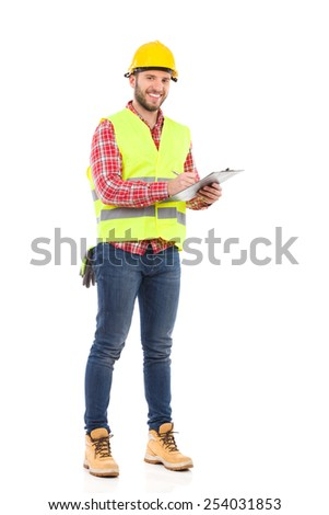 Foreman taking a notes. Smiling construction worker in yellow helmet and lime waistcoat posing with a clipboard. Full length studio shot isolated on white.