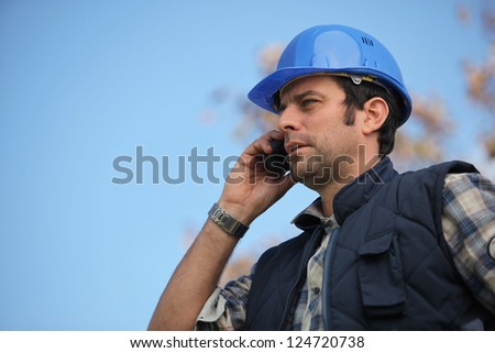 Foreman talking on his mobile phone - stock photo
