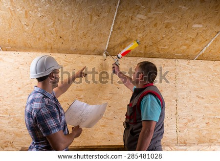 Foreman Wearing White Hard Hat and Holding Building Plans Instructing Worker How to Apply Caulk to Seam in Unfinished Wood Ceiling in New Home - stock photo