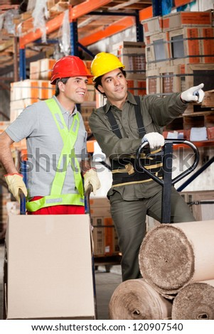 Foreman with fork pallet truck showing something to coworker at warehouse - stock photo