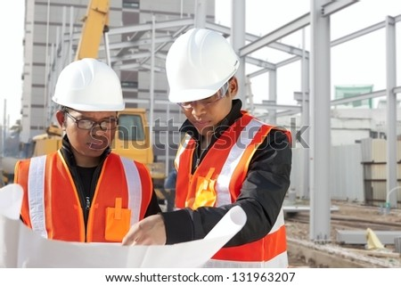 Foreman with safety vest discussion under construction