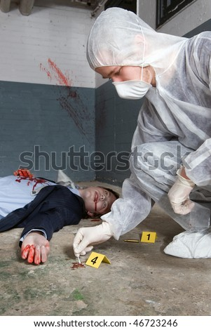 Forensic expert collecting evidence in a crime scene around a dead businessman - stock photo