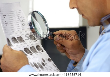Forensic investigator comparing fingerprints during a criminal investigation.                            - stock photo