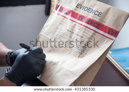 forensic 's hand in black glove writing on evidence bag and seal by red tape in crime scene investigation - stock photo