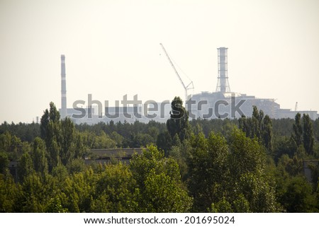 Forest and Chernobyl nuclear reactor in the background, it was covered with sarcophagus and abandoned after nuclear disaster in Chernobyl at 26.04.1986 (taken from Pripyat) - stock photo