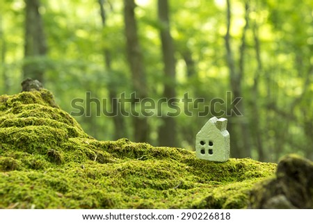 forest and miniature house - stock photo