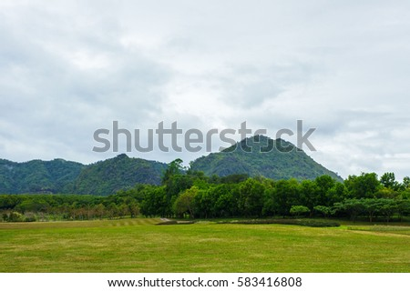 Forest and mountain in Thailand with green grass in foreground and blue sky in background with copy space. For landscape.