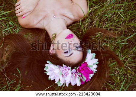 forest beauty fairy: image of beautiful brunette young woman with naked shoulders & flowers crown having fun relaxing looking at camera lying on green summer outdoors copy space background - stock photo