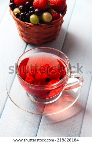 Forest berries in wicker basket and glass cup with red fruit tea, on wooden background - stock photo