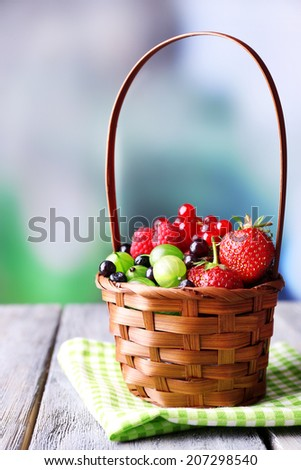 Forest berries in wicker basket, on wooden table, on bright background