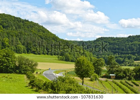 Forest, field, road and blue sky. Bavaria, Germany
