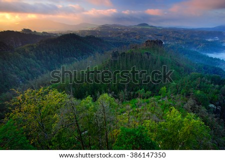 Forest hills, beautiful morning view over sandstone cliff into deep misty valley in Bohemin Switzerland, foggy background, the fog is orange due to sunrise, star sun on sky, Germany - stock photo
