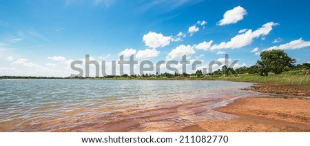 Forest lake on the blue cloudy sky - stock photo