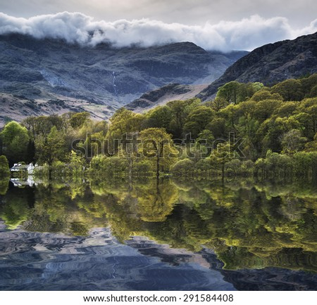 Forest landscape reflected in calm water of Coniston Water in Lake District - stock photo