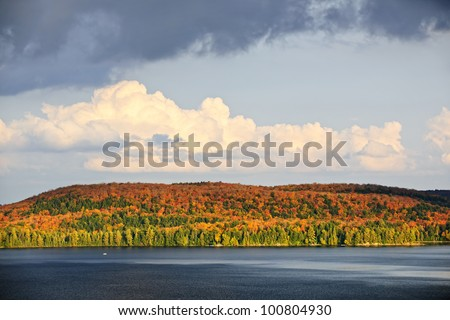 Forest of colorful autumn trees with lake and dramatic sky - stock photo