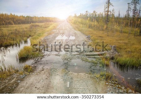 Forest Road old, broken forest road leading through the creek into the depths of the Siberian Forests - stock photo