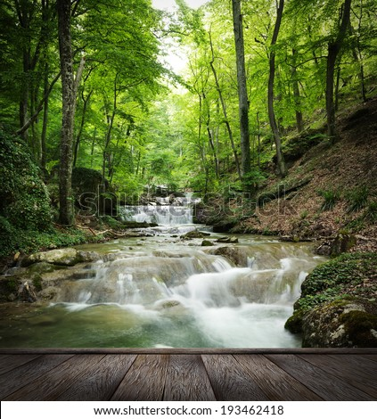 forest waterfall and rocks covered with moss and wood pier - stock photo
