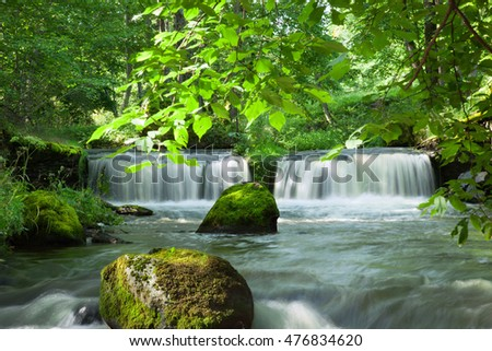 Forest waterfall and stones covered with moss.