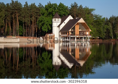 Forest wooden home at the lake. Day light - stock photo