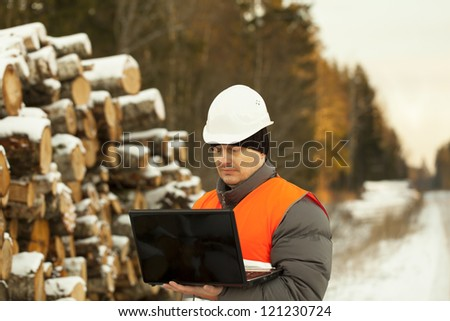 Forester with the computer near the log pile - stock photo