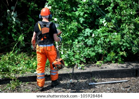forestry worker cuts plants with a machine - stock photo