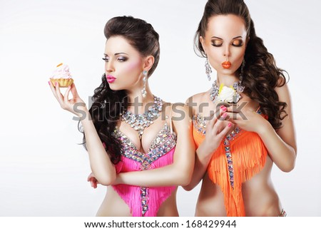 Foretaste. Two Women holding Appetizing Cupcakes with Whipped Cream
