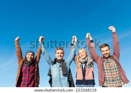 Forever young. Low angle view of four young happy people holding hands and raising them up with blue sky as background
