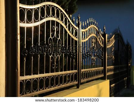 Forged decorative iron fence at sunset - stock photo