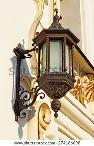 Forged old lamp on the wall. Architecture details. - stock photo