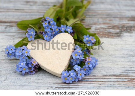forget me not and heart lying on wood - stock photo