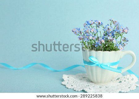 Forget-me-nots flowers in cup, on blue background - stock photo