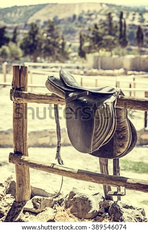 Forgotten by Time / a forgotten horse saddle on a wooden fence  - stock photo