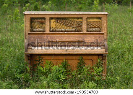 Forgotten - old upright piano left in a field. - stock photo