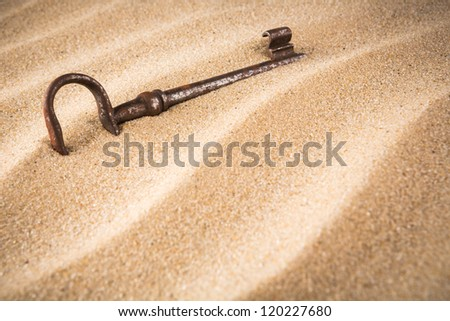 forgotten, unwanted, old, antique, key in a sand dune