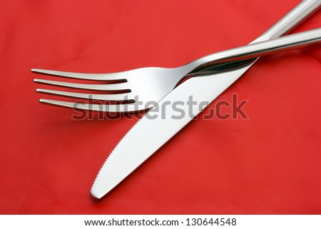 Fork ad knife on red tablecloth - stock photo