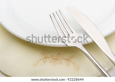 fork and a knife lie on serviette and a plate. A photo close up - stock photo