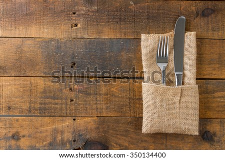 fork and knife in napkin on wood - stock photo