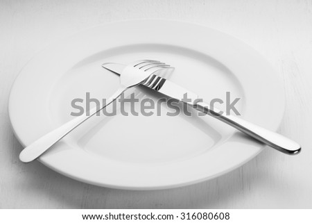 Fork and knife lying on the empty white plate - stock photo