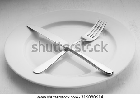Fork and knife lying on the empty white plate