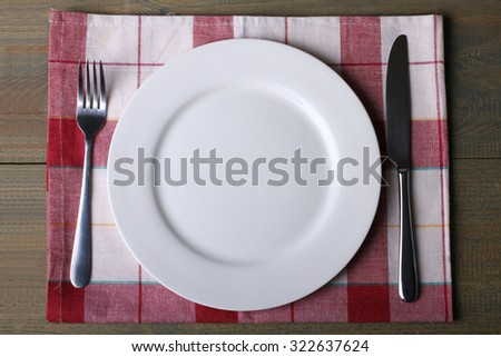 fork and knife next to the plate on napkin on wooden table