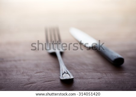 Fork and knife on a rustic wooden table. Extremely shallow depth of field for dreamy feel. - stock photo