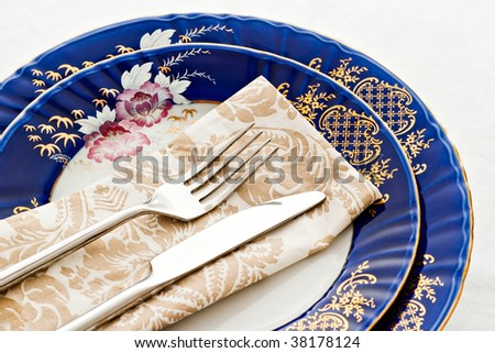fork and knife on fine porcelain plates - stock photo