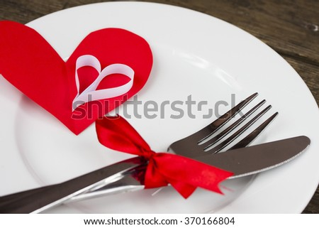 Fork and knife on plate and hearts on a table  - stock photo