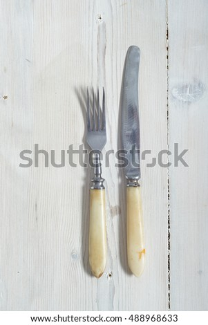 Fork and knife on the light old wood background