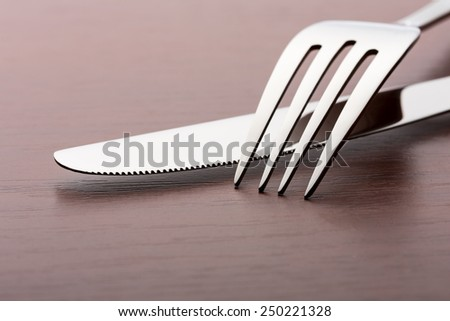 Fork and knife on wood - stock photo