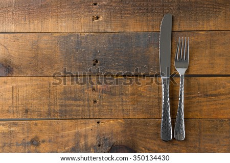 fork and knife on wood background - stock photo